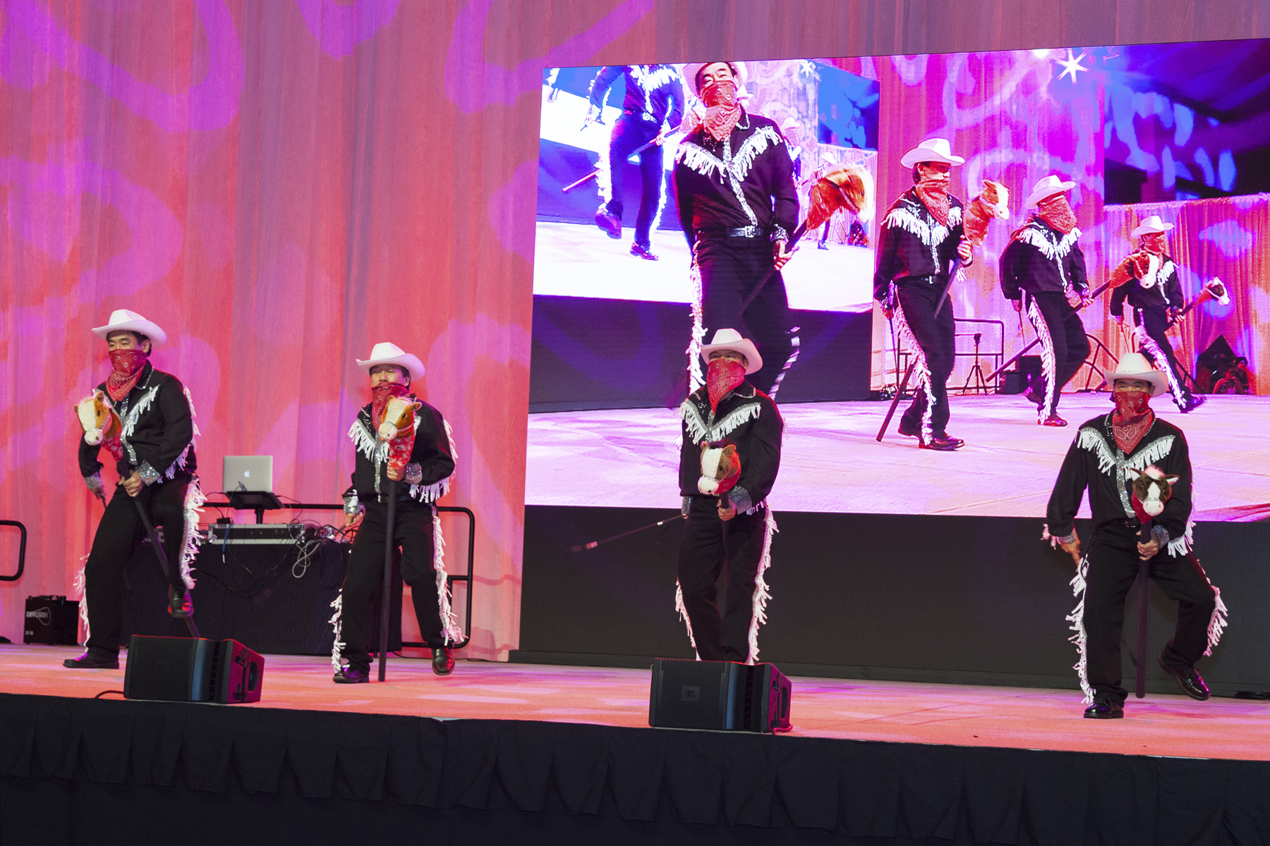 """2016 AN EVENING AROUND THE WORLD: Yee Haw! (L to R) CFS cowboys Michael Young (Albert C. Kobayashi, Inc.), Glen Kaneshige (Nordic PCL Construction, Inc.), Joe Young (Deloitte & Touche LLP), & Walter Yamane (Hawaiian Dredging Construction Company, Inc.) ride onto stage with their """"horses"""" to the music of Boot Scootin' Boogie (Brooks & Dunn')!"""
