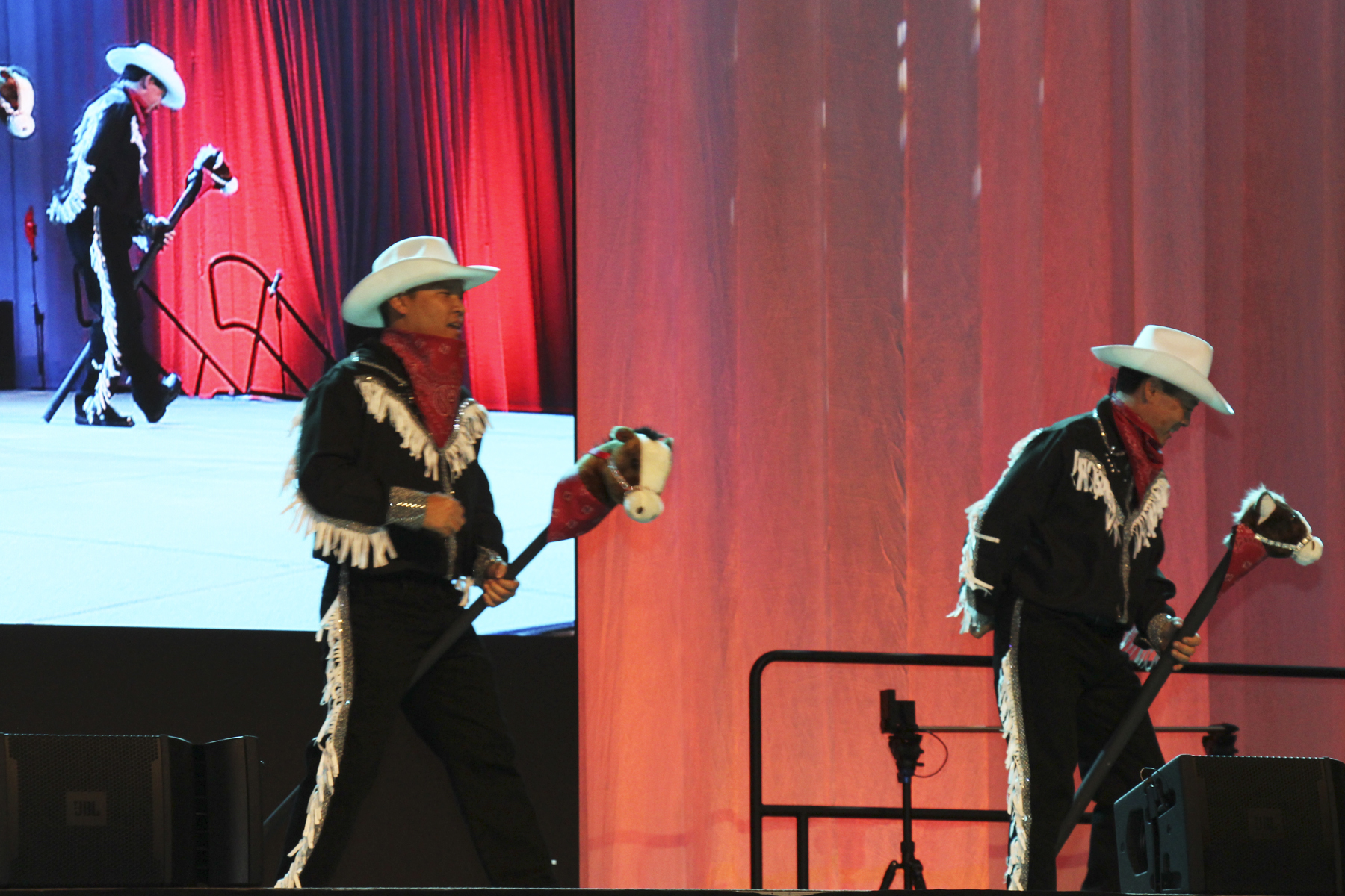 """2016 AN EVENING AROUND THE WORLD: Ride em cowboy! CFS cowboys Joe Young (Deloitte & Touche LLP) & Walter Yamane (Hawaiian Dredging Construction Company, Inc.) ride their """"horses"""" on stage!"""