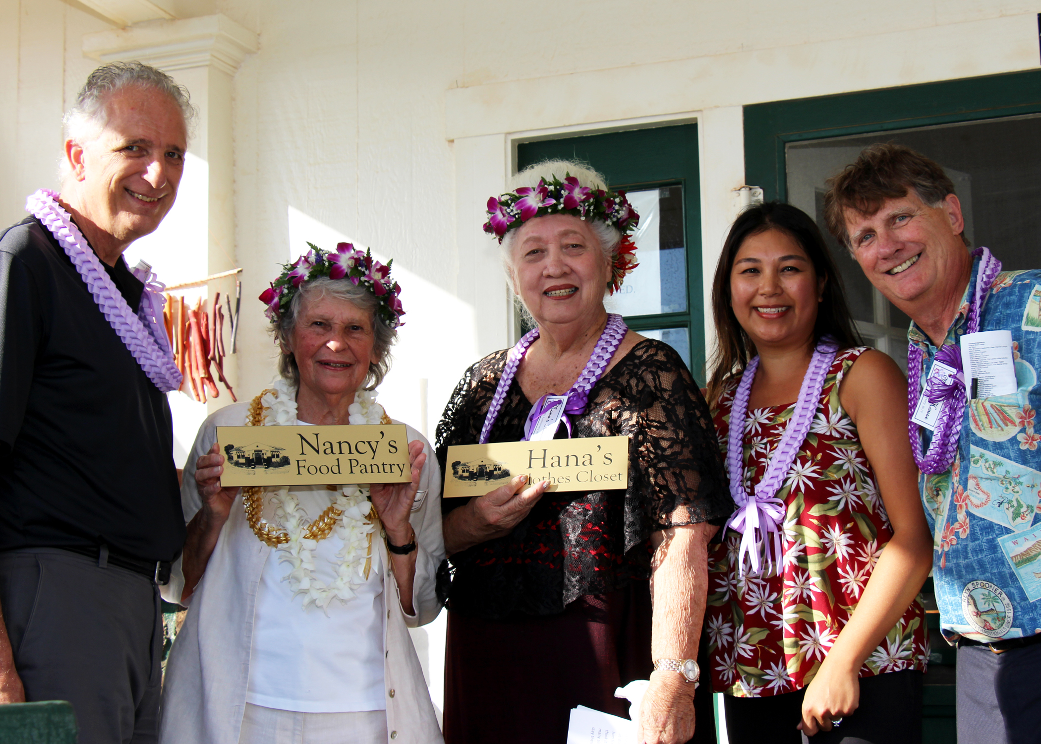 "Nana's House Co-Founder Nancy Golden (2nd from left) & Hana Montgomery (3rd from left) are presented with plaques renaming the food pantry & clothes closet to ""Nana's Food Pantry"" & ""Hana's Clothes Closet,"" respectively. Also in the photo (L to R) William Harrington (Kaua'i Family Centers Director), Novelyn Hinazumi (Director of Kaua'i Programs), & Howard Garval (President & CEO)."